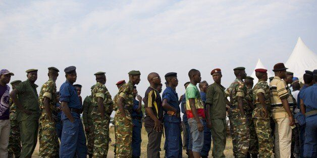 Civilians, army soldiers and police queue to vote in the opposition stronghold of Musaga in Bujumbura on June 29, 2015. Votin