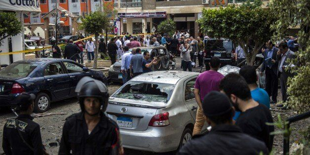 Egyptian security forces stand guard at the site of a bomb that targeted the convoy of the Egyptian state prosecutor, Hisham