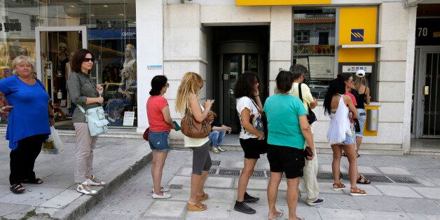 People line up at an ATM outside a Piraeus bank branch in Athens, Monday, June 29, 2015. Anxious Greeks lined up at ATMs as t