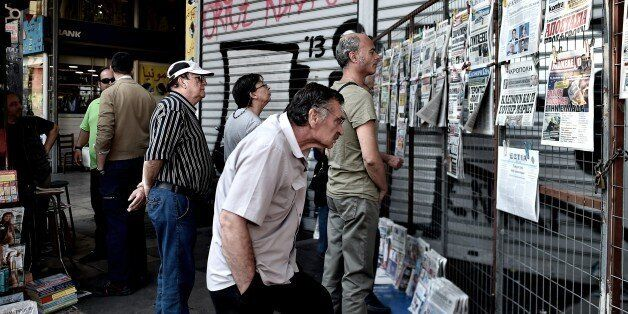 People read newspapers in central Athens on June 30, 2015. European leaders want to 'sink' Greece's ruling Syriza party to bl