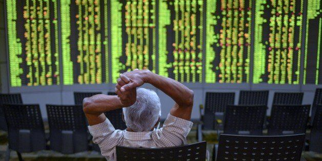 A man gestures as he monitors stock movements at a private trading firm in Kuala Lumpur on June 30, 2015. Most Asian markets