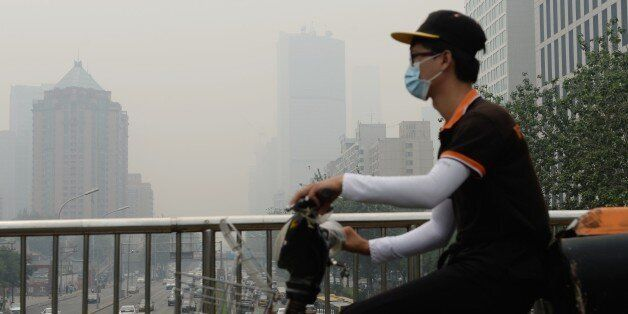 This picture taken on June 23, 2015 shows a cyclist wearing a mask in Beijing covered by heavy smog. China's cities are often