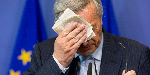 European Commission President Jean-Claude Juncker wipes his face during a media conference at EU headquarters in Brussels on