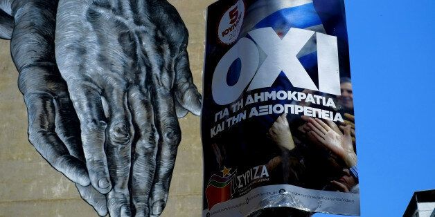 Hands painted on the wall of a building seen behind a poster for a NO vote in the upcoming referendum, in central Athens, Wed