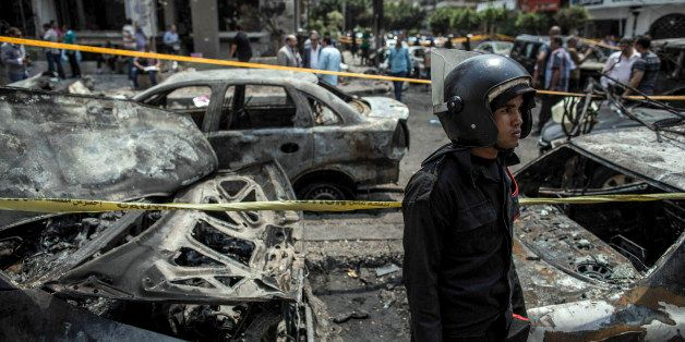 An Egyptian policeman stands guard at the site of a bombing that killed Egypts top prosecutor, Hisham Barakat, in Cairo, Egyp