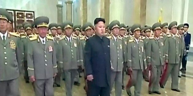 In this Tuesday, July 8, 2014 image made from video, North Korean leader Kim Jong Un, center, visits...