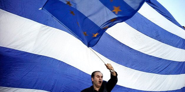ATHENS, GREECE - JUNE 22:  A man waves a EU flag as pro-Euro protesters take part in a rally in front of the Parliament on Ju
