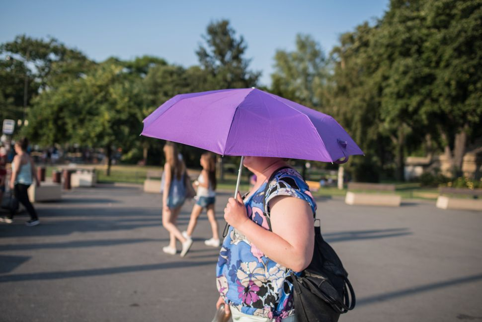A woman carries an umbrella to protect herself from the sun while walking near the Seine river in Paris on Wednesday, July 1,