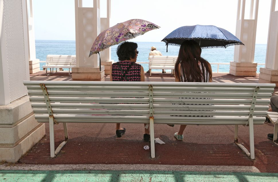 Two women take shelter under umbrellas on the promenade des Anglais in Nice, France, on Thursday, July 2, 2015.