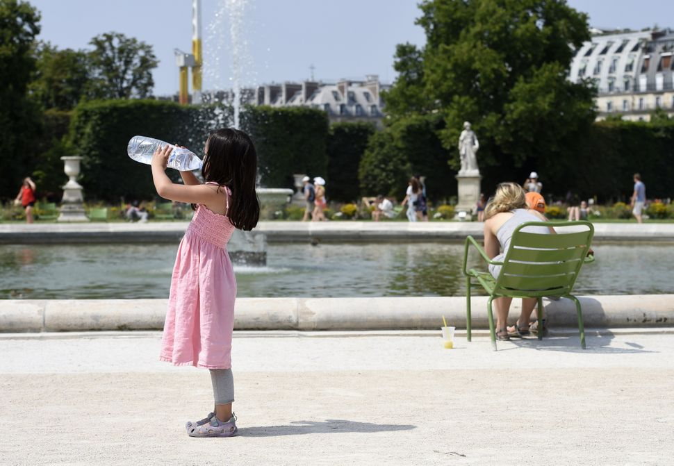 A girl stays hydrated in the heat near a fountain in the Tuileries Garden in Paris on Thursday, July 2, 2015.