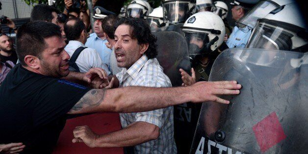 Anti-EU protesters scuffle with police outside the European Comission offices in Athens on July 2, 2015.  Greece's government