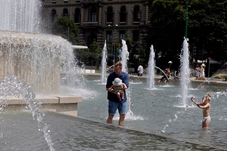 A man holding a baby cools-off in a fountain in Milan, Italy, Friday, July 3, 2015.  (AP Photo/Luca Bruno)