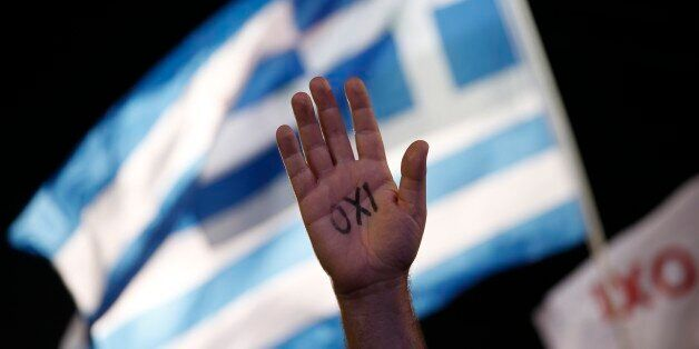 A demonstrator rises his hand reading the word ''No'' as a Greek flag waves during a rally organized by supporters of the No
