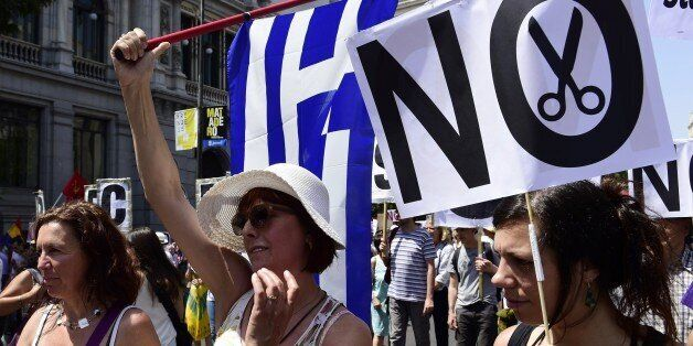 A woman holds a placard reading 'No cuts' during a demonstration in support of Greece, in Madrid on July 5, 2015. Today, near