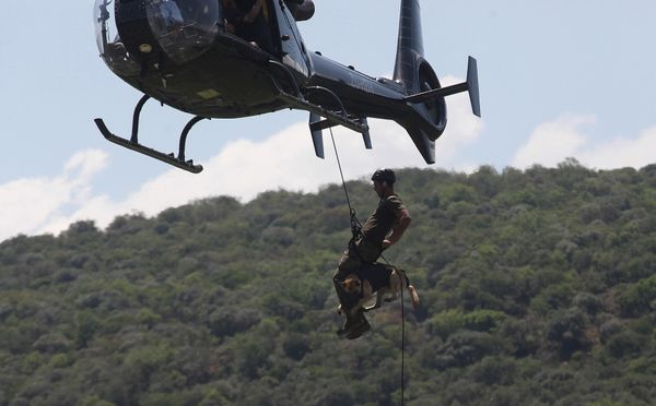 In this photo taken Wednesday, Nov. 26 2014 a handler and his dog abseil from a helicopter, in a simulated exercise showing t
