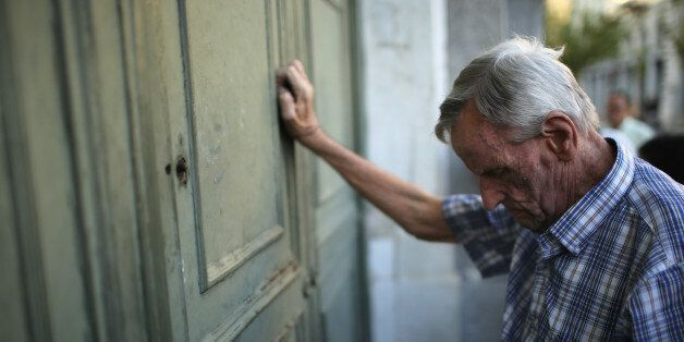 ATHENS, GREECE - JULY 07:  A senior citizen leans against the door of a closed bank as he queues up to collect his pension ou