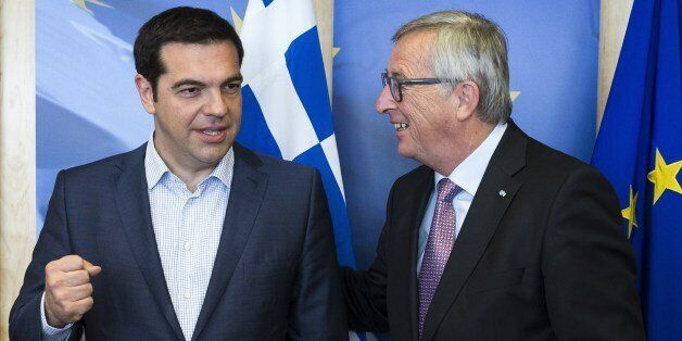 Greece's Prime Minister Alexis Tsipras (L) is welcomed by European Commission President Jean-Claude Juncker (R) ahead of a me