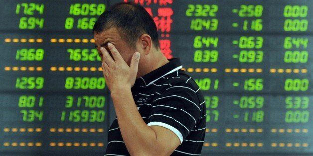 An investor reacts in front of a screen showing stock market movements in Fuyang, eastern China's Anhui province. Chinese sha