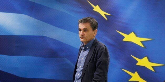 New Greek Finance Minister Euclid Tsakalotos arrives for a hand over ceremony in Athens, Monday, July 6, 2015. Following Sund