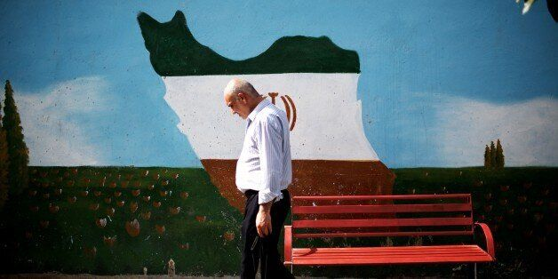 An Iranian man walks past a mural displaying the Iranian map adorned in the colours of the country's national flag, on June 2