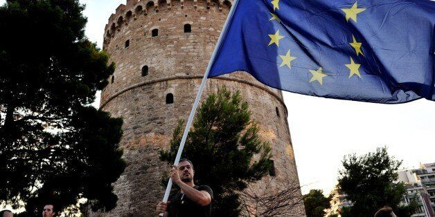 A pro-European Union protester holds an EU flag, during a demonstration outside the White Tower in Thessaloniki on July 9, 20