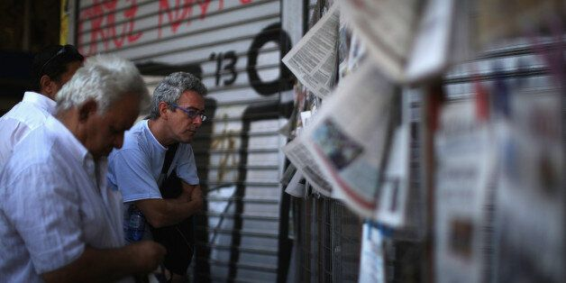 ATHENS, GREECE - JULY 10:  Men read the newspapers outside a newsagent on July 10, 2015 in Athens, Greece. Greek prime minist