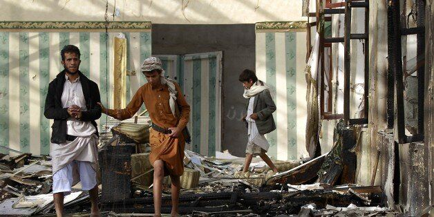 Armed Yemenis walk on the rubble of a wedding hall which was reportedly hit by a Saudi-led coalition air strike in the capita