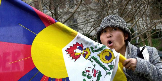 WASHINGTON, UNITED STATES:  A protester waving a Tibetan flag chants slogans calling for the release of jailed Tibetan Buddhi