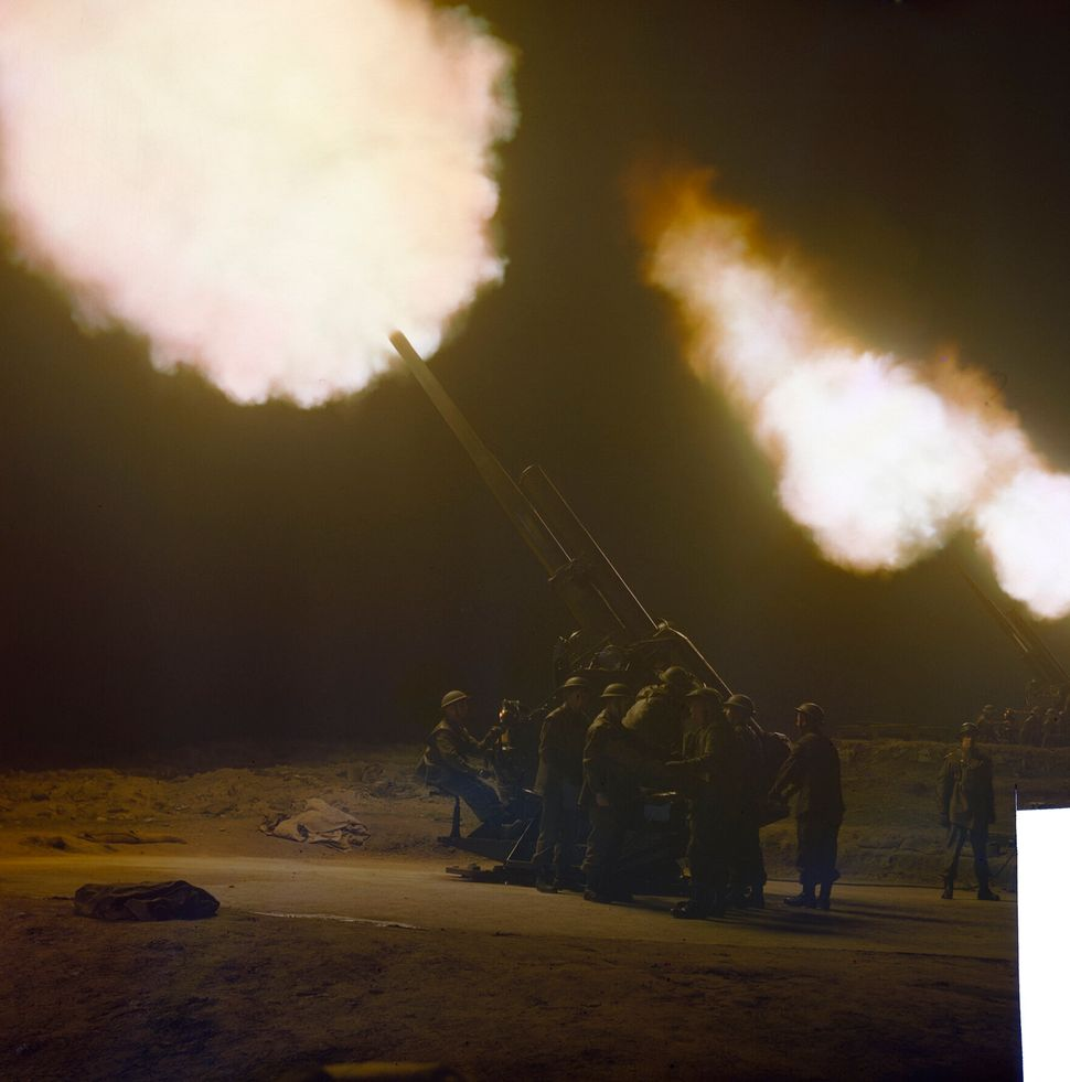 A battery of 3.7 inch anti-aircraft guns firing at night.