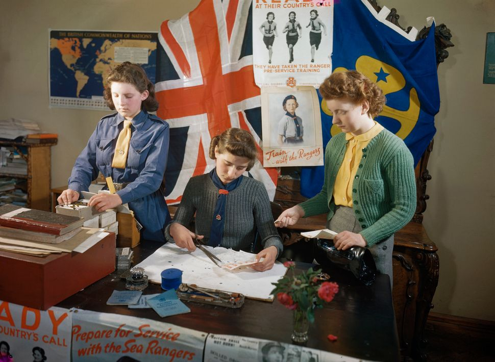 The War Effort: A Girl Guide and a Sea Ranger selling saving stamps.