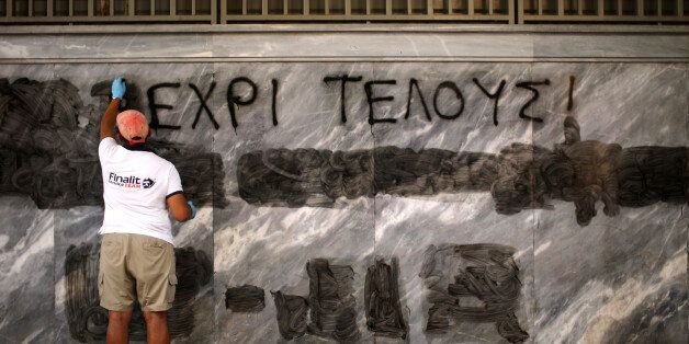 ATHENS, GREECE - JULY 14:  A man cleans off the latest batch of anti-austerity graffiti from the walls of the Bank of Greece