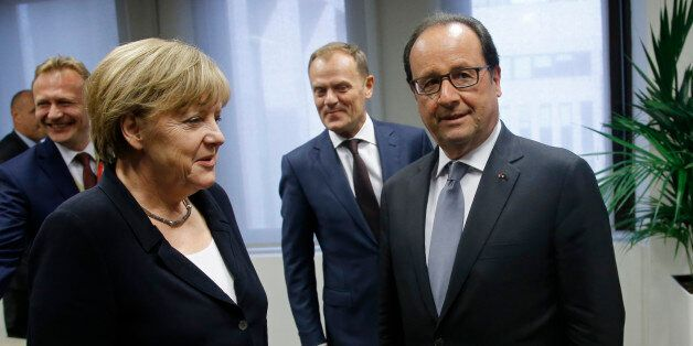 German Chancellor Angela Merkel, center left, speaks with French President Francois Hollande, center right, during a meeting