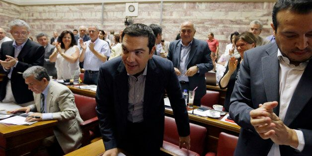 Greece's Prime Minister Alexis Tsipras arrives for a meeting as his lawmakers of Syriza party applaud him at the Greek Parlia