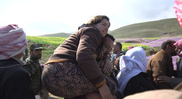 A rescued woman is carried to safety