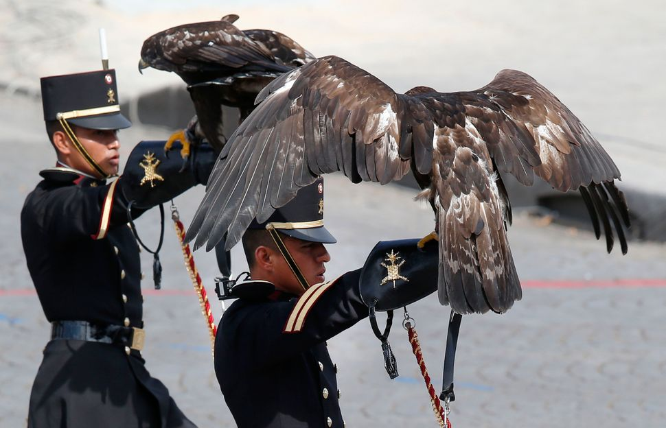 Mexican soldiers display birds of prey as they walk down the Champs-Elysees avenue during Bastille Day parade Tuesday, July 1