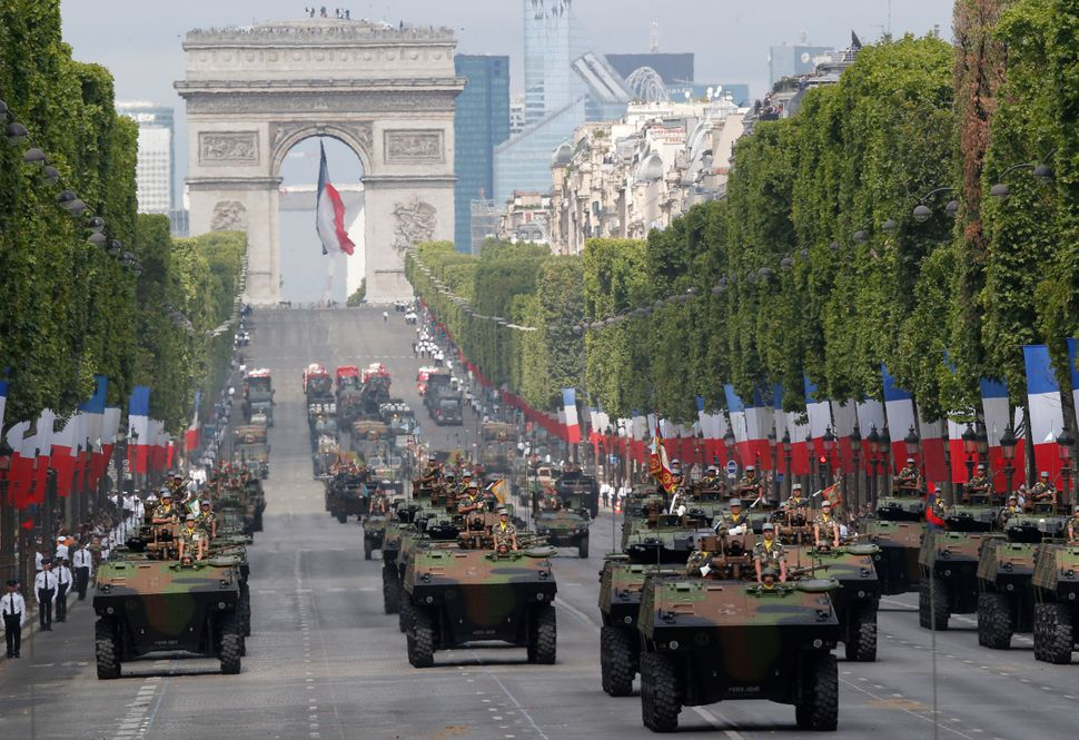 Light armed vehicles drive down the Champs-Elysees. (AP Photo/Michel Euler)