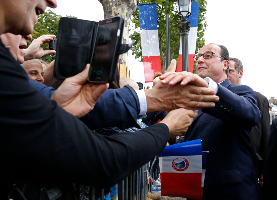 French President Francois Hollande, right, shakes hands with spectators after the Bastille Day parade. (Pascal Rossignol, Poo