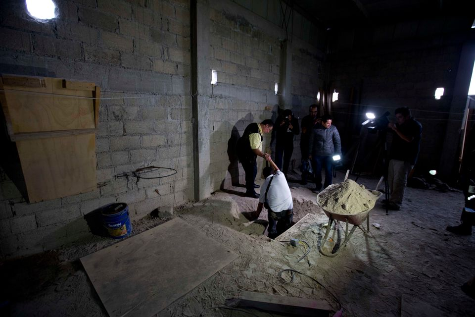 """Journalists exit the tunnel where, according to authorities, drug lord Joaquin """"El Chapo"""" Guzman made his escape from the Alt"""