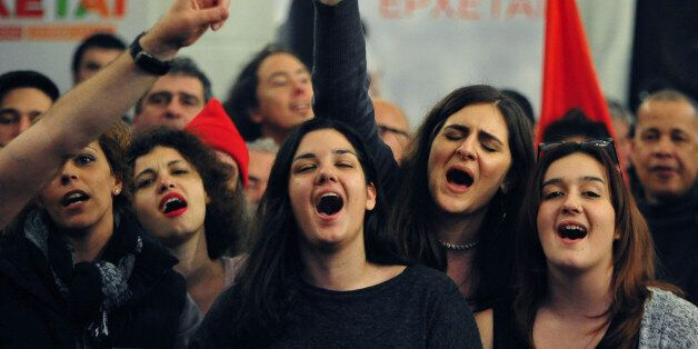 Supporters of left-wing Syriza party sing at the election kiosk in Athens, Sunday, Jan. 25, 2015. Greek election officials sa