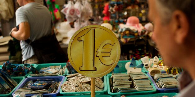People buy items for one euro at a store in central Athens, Thursday, July 16, 2015. Greece's troubled left-wing government
