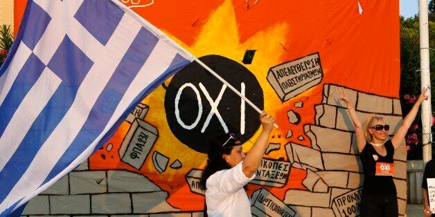 A demonstrator makes the victory sign in front of a banner, depicting a medal ball reading ''NO'' and destroying a wall with