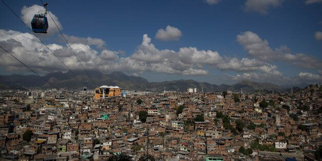 A cable car transports commuters over homes in the Complexo do Alemao shantytown in Rio de Janeiro, Brazil, Thursday, May 21,