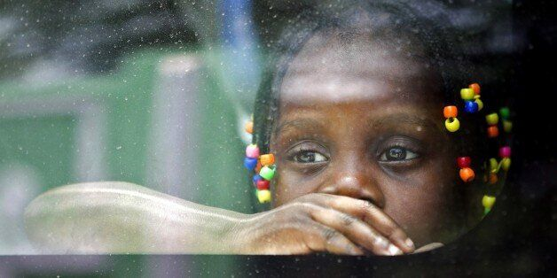 An Haitian girl looks from the window of a vehicle as her family is transported to be voluntarely repatriated in Santo Doming