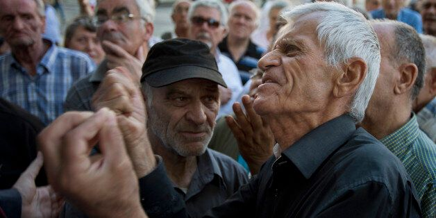 Elderly people argue with a bank worker as they wait to be allowed into the bank to withdraw a maximum of 120 euros ($134) fo