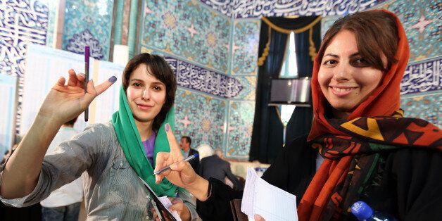 Iranian women display their ink-stained fingers as they cast their votes in the first round of the presidential election at a