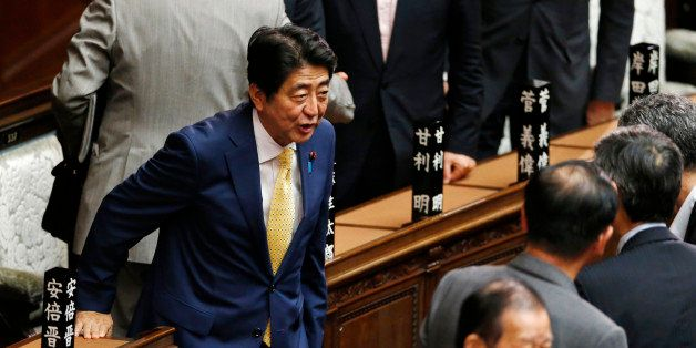 Japanese Prime Minister Shinzo Abe, left, greets his ruling party lawmakers after a plenary session at the lower house in Tok