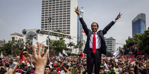 JAKARTA, INDONESIA - OCTOBER 20:  Indonesian President Joko Widodo waves to crowds while on his journey to Presidential Palac
