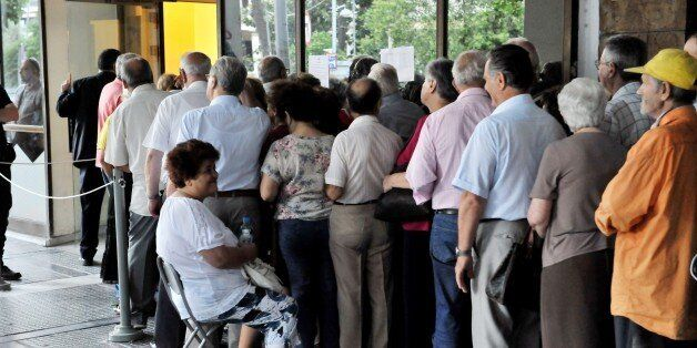 People queue outside of a National bank branch in Thessaloniki on July 10, 2015. Lawmakers in Greece will vote whether to bac