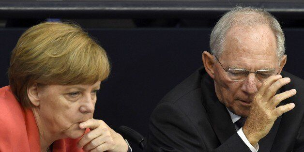 German Chancellor Angela Merkel (L) confer with finance minister Wolfgang Schaeuble during a debate in the  Bundestag, the Ge