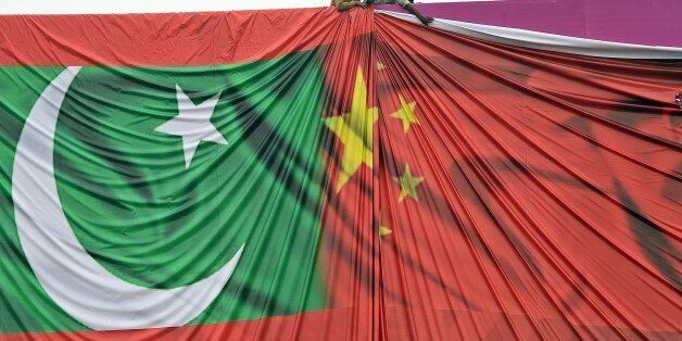 Pakistani labourers arrange a welcome billboard featuring the Chinese and Pakistani national flags ahead of the forthcoming v